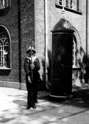 """Da Søværnets enestående modelsamling i foråret 1940 blev flyttet fra Holmen og til Frederiksborg Slot, blev den gamle modelbygning ledig. Da den lå centralt på Holmens område, blev den indrettet til beboelse for Holmens vagtkompagni. Her ses en dansk """"marineinfanterist"""" på vagt foran Modelkammeret."""