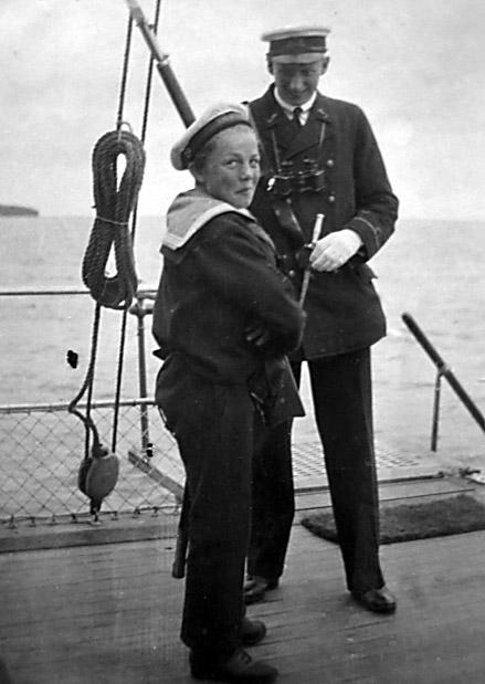 """Prins Knud ombord i krydserkorvetten """"Valkyrien"""" på dens sidste togt 1923. Den anden person på billedet er DOE nr. 65 (DOE er """"Dæksofficerselev"""") Hans Robert Petersen. HRP blev senere Radiotelegrafist I (ligestillet med Kvartérmester I). I bogen """"Valkyrien og dens sidste Togt"""", af Carl Østen, udg. 1959 på Hirschsprungs forlag, er de to personer omtalt som """"højeste og mindste ombord""""."""