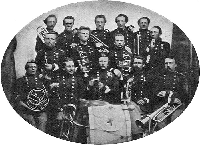 """1. Liniebataljons Musikkorps (""""Kjøbenhavnerne"""") som havde garnison i Rendsborg 1852-1863. Det var disse herrers musikinstrumenter der 'flittigt dansede på de akademiske rygge' i Kiel. Fotoet er fra 1863. Formentlig ses Stabshornblæser Petersen i første række midtfor stortrommen (Indstillet til Tapperhedsmedaljen i sølv efter slaget v. Sankelmark (som bekendt blev denne medalje aldrig uddelt til de indstillede.)(Foto fra Lindhardt 'Klingende Spil' Kbh. 1932)"""