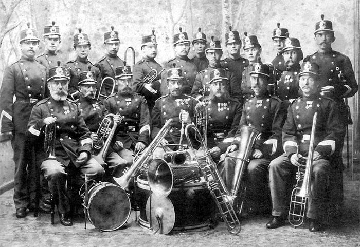 8. Regiments Musikkorps, Aarhus, ca. 1890. Stabshornblæser Julius Bergmann sidder midt i forreste række. Overhornblæser Johann Friedrich Arndt ses med sit piccolohorn siddende i 1. række, nr. 1 fra venstre. Nr. 2 fra venstre i bagerste række er sønnen Marius Arndt. (Foto: Aarhus Orkesterforening)