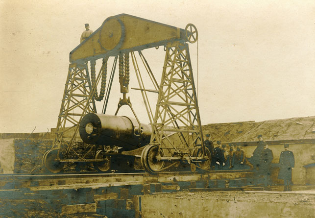 Opstillingen af en ud af 12 styk 290 mm howitzers på Charlottenlund Fort, et kystbatteri opført 1883-86 og nedlagt i 1932. Fortet var en del af et dansk forsvar, hvor man på forhånd havde opgivet Jylland, Fyn og Sjælland, og koncentrerede sig om at befæste og forsvare København. En idé som Aage Westenholz vendte sig stærkt i mod. Wikipedia.
