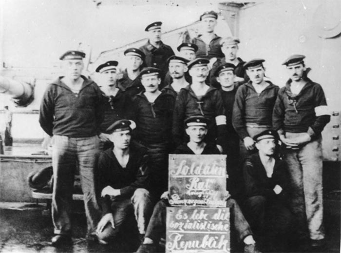 "Revolutionære matroser i Kiel (Wikipedia). På skiltet står: ""Soldaterråd krigsskib prinsregent Luitpold. Leve den socialistiske republik""."