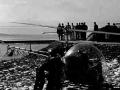 En tilskadekommet fra en vådeskudsulykke bliver transporteret bort med en Augusta Bell 47 helikopter. Helikoptertypen var i brug af forsvaret fra 1952-58.