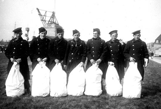 Foto visende Preuthun og kammerater ved løsladelsen fra interneringen den 26. oktober 1943. I baggrunden anes den sænkede kystforsvarsskib PEDER SKRAM.