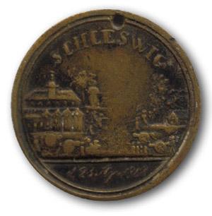 """Tysk erindringsmedalje for kampen ved Slesvig. Bagside teksten var: """"Til de tyske helte"""". Den blev lavet af private og solgt til de tyske soldater. Da man ikke kunne sælge flere til tyskerne, lavede man teksten om til: """"Til de danske helte"""", og solgte dem til danskerne!"""