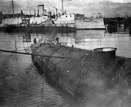Dykkerens agterdæk fotograferet på Holmen efter kollisionen. Den tomme lugekarm ses tydeligt. I baggrunden logiskibet Hekla og den britiske ubåd E.13. (5. Eskadre).