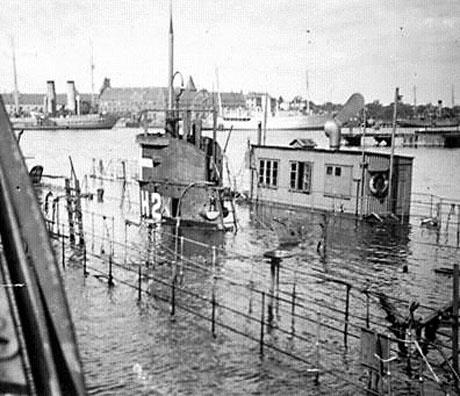 HAVFRUEN i den sænkede dok. Her ses også tydeligt dokkens maskinhus, som Tuxen måtte bryde ind i for at få sænket dokken. (Orlogsmuseet)
