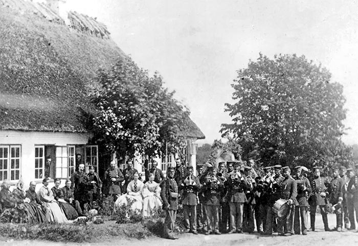 """5. Regiments Musikkorps på Als under våbenhvilen 1864 – identisk med 5. Bataljons musikkorps (se foto fra 1862 senere). 5. og 7. Regiment udgjorde tilsammen 6. Brigade, der bevogtede Als under våbenhvilen. Den høje hornblæser i 2. geled er formentlig Gundelach. Soldaten med gevær ved skulder menes at være genkendt som menig Jens Nissen Hansen Tagmose af 8. Regiment. 5. Regiments musikkorps har igen fået instrumenterne frem. Bagsiden af stereobilledet på Rigsarkivet oplyser: """" Oberst A. C. J Mykrets middag på Als (juni?) 64″. (Foto: Rigsarkivet)"""