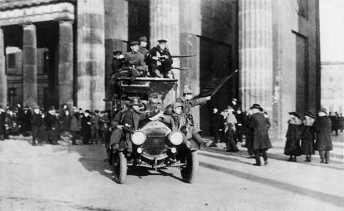 Berlin, 9. november 1918. Revolutionære med den røde fane foran Brandenburger Tor (Wikipedia, Bundesarchiv). Efter matrosoprøret i Kiel 3. november spredte urolighederne sig overalt i Tyskland.; kejseren abdicerede 9. november og soldater- og bonderåd oprettes overalt i Tyskland efter sovjetisk forbillede. Højreorienterede frikorps blev sat ind mod de venstreorienterede revolutionære og nedkæmpede bl.a. Spartakist-oprøret i Berlin i januar 1919 og Den Bayerske Sovjetrepublik i maj 1919.