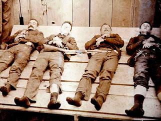 Billede (Wikipedia) t.v.: Medlemmer af Dalton-banden, Bob og Grat Dalton i midten, efter at være blevet skudt den 5. oktober 1892 efter et fejlslagent bankrøveri i Coffeyville, Kansas, hvor Chris begyndte sin karriere i det amerikanske. Chris Madsen blev US Marshall i Oklahoma i 1891.